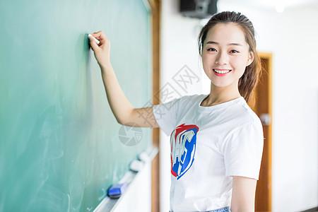 黑板前拿粉笔写字的女生图片