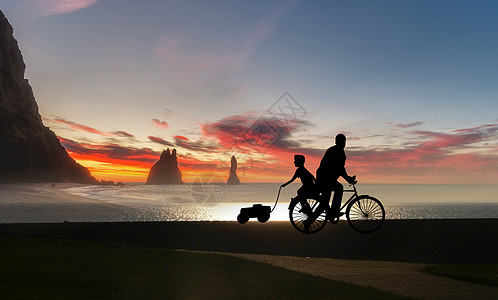 夕阳下骑车父子剪影图片