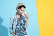 拿着桃子的青年男性图片