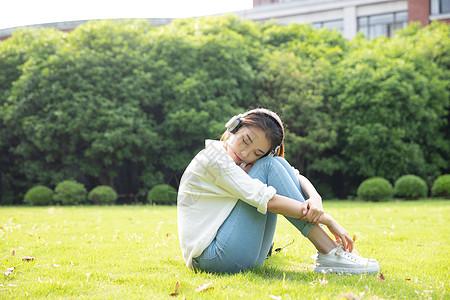 草地上青春学生听音乐图片