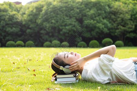 青春学生躺草地上听音乐图片