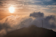 黄昏时山顶云海中的发电风机图片
