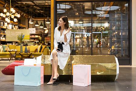 青年女性商场购物休息打招呼图片