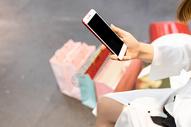 青年女性购物休息看手机特写图片