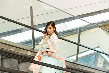 青年女性购物坐扶梯打电话图片