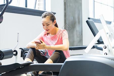 女性青年健身休息看手机图片