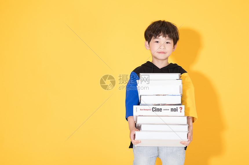 儿童教育小男孩手抱书本图片