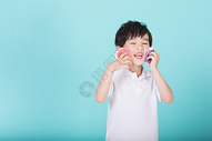 儿童小男孩手持甜甜圈玩耍图片