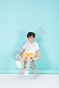 坐在凳子上的小男孩儿童图片