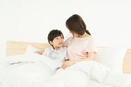 妈妈陪伴儿子在床上看书500946372图片