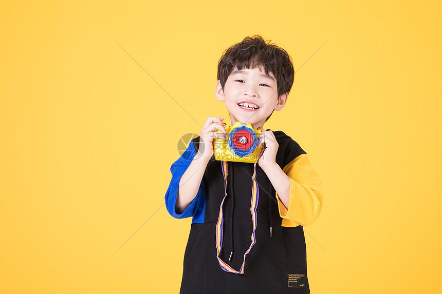 小男孩儿童手拿玩具相机拍照图片
