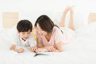 妈妈陪伴儿子在床上看书图片