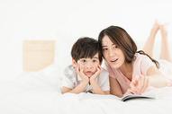 妈妈陪伴儿子在床上看书500946404图片