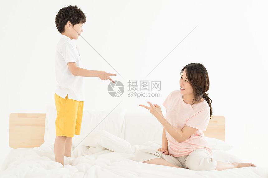 妈妈陪伴儿子在卧室床上玩耍图片