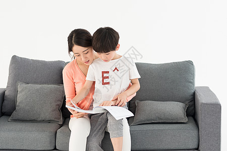 妈妈陪伴儿子在沙发上看书图片