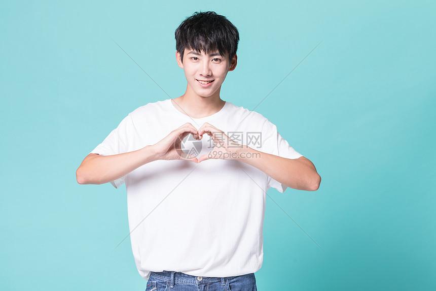 青年男性比心手势图片