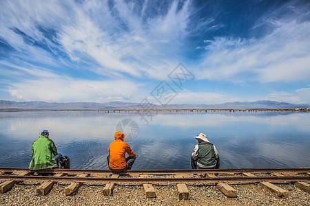 茶卡盐湖旁铁轨上休息的人图片