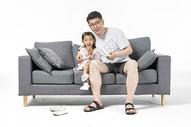 爸爸和女儿在沙发上看电视图片