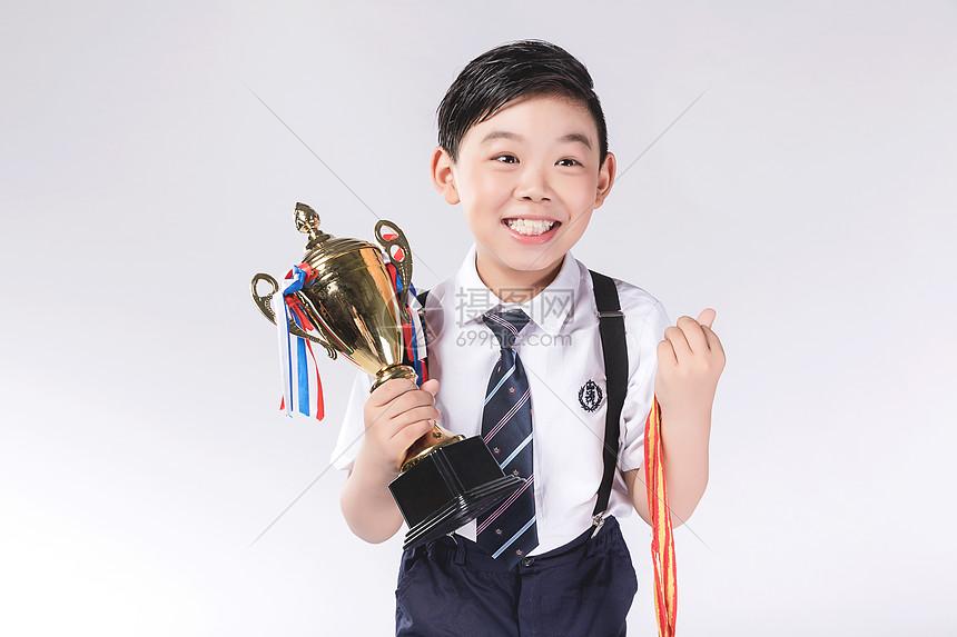 男孩子获得奖杯奖牌图片