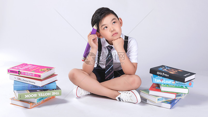 男孩在书堆中学习图片