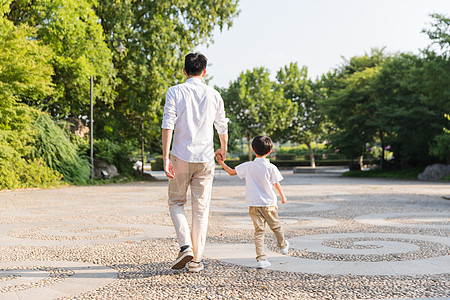 公园里牵手散步父子背影图片