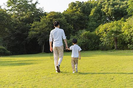 父亲节公园里牵手散步父子背影图片