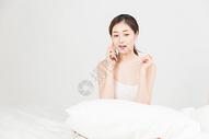 年轻女性床上打电话图片