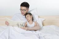 爸爸给女儿在床上讲故事图片