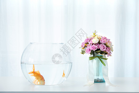 桌子上的金鱼与花卉图片