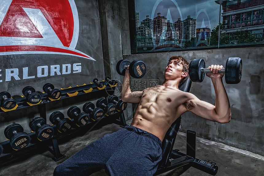 健身房强壮男性哑铃运动图片
