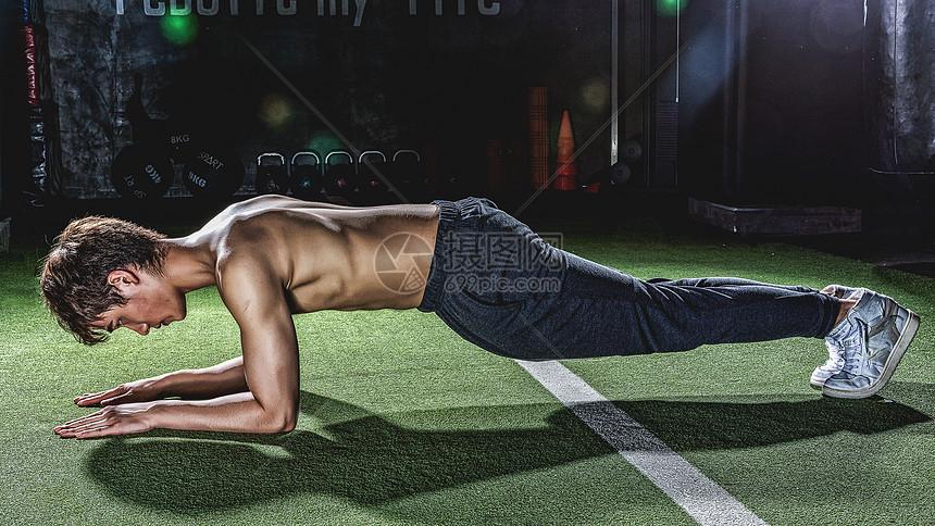 健身房强壮男性做俯卧撑图片