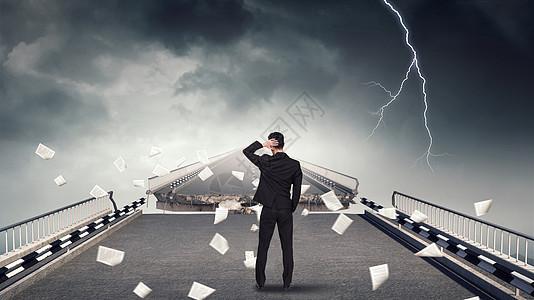 乌云密布的天空下断裂的桥和商务人士图片