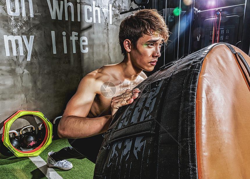 健身房强壮男性推轮胎运动图片
