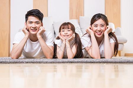 幸福的一家三口趴在地毯上图片