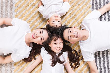 幸福的一家人躺在地毯上图片