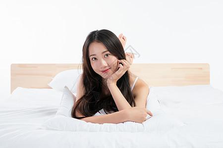 年轻女性趴在床上玩图片