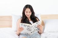 年轻女孩床上看书图片