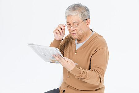 老年人戴眼镜看报纸图片