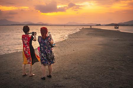 广东惠东盐洲岛海岸夕阳晚霞下拍照的游人图片
