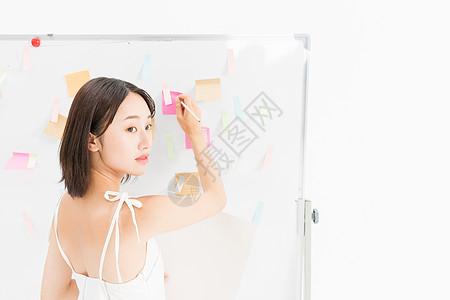 女设计师在白板前记录图片