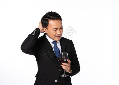 商务男手拿酒杯思考图片