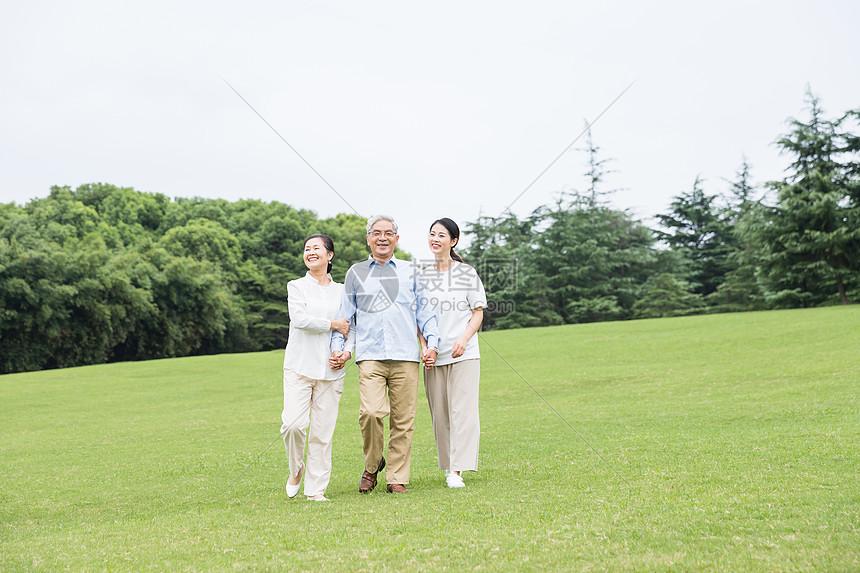 草地上幸福一家人散步图片