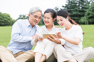 草地上幸福一家人看手机图片