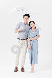年轻父母打伞接孩子动作图片