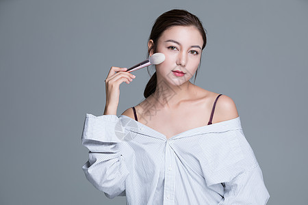 年轻美女手拿化妆刷图片