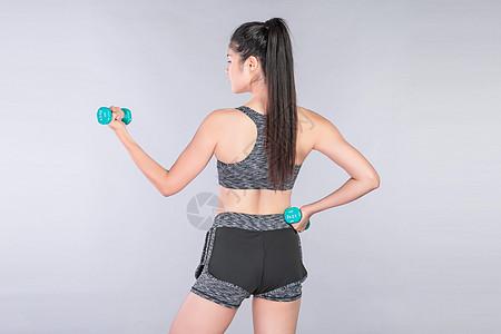 运动健身举哑铃的年轻美女图片