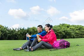 户外远足情侣休息喝水图片