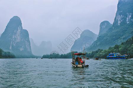 春日微雨中的桂林漓江竹筏漂流图片