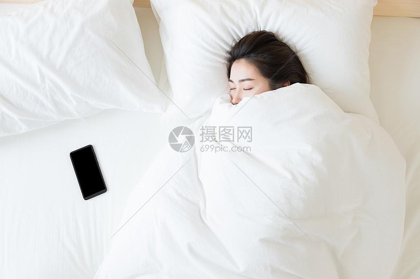 年轻女性睡觉与手机图片
