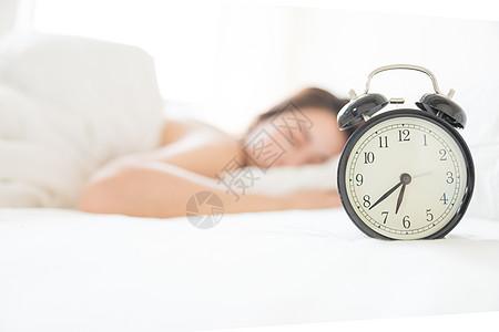年轻女性起床困难与闹钟图片